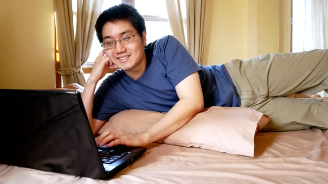 Happy man with eyeglasses using laptop computer for online chat messaging on bed - domestic indoor scene video