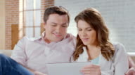 Happy man woman enjoying time together, online shopping, tablet video