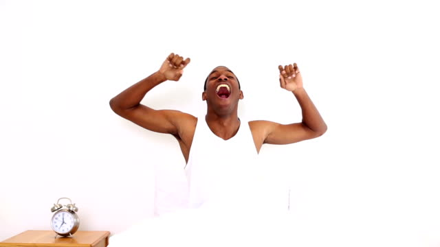Happy man yawning and stretching sitting in bed video