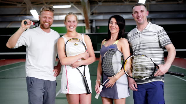 Happy married couples in sports clothes stand in a tennis club with rackets in their hands, men and women in anticipation of a sport game video