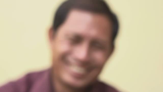 Happy mature Asian man smiling and looking at camera video