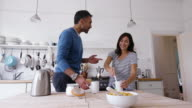 Happy mature couple talking in kitchen video