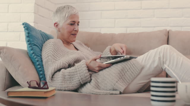 Happy mature woman typing an e-mail on laptop  and after that taking a nap on sofa. video