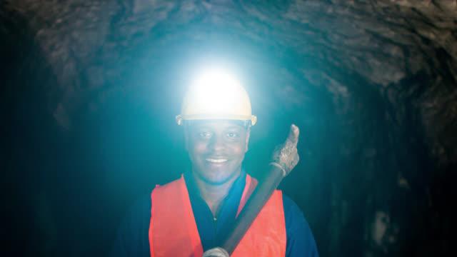 Happy miner working at a mine underground video