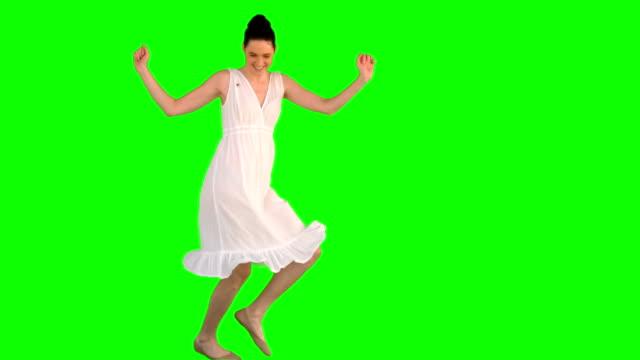 Happy model in white dress dancing video