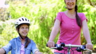 Happy mother and daughter on a bike ride video