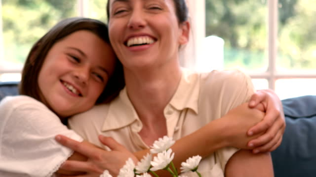 Happy mother and daughter sitting on the couch with flowers video