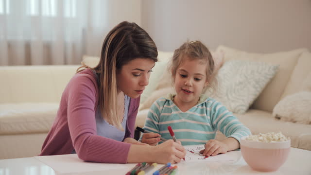 Happy mother and daughter talking while drawing together in the living room. video
