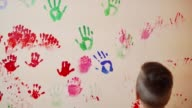Happy mother and her cute boy having fun together leaving their colorful handprints on the wall. Young happy family. Mother and child concept video