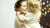 Happy mother and her little daughter go round in a decorated room with lights video