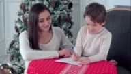 Happy mother and her son writing letter to Santa video