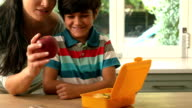 happy mother putting apple in her sons lunch box video
