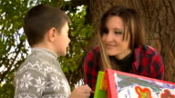 Happy mother with her son drawing on canvas and smiling for each other video