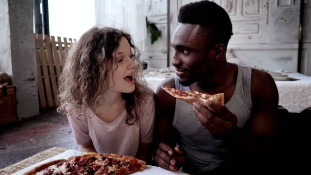 Happy multiethnic couple in pajamas eating fast food. Hungry woman waits the meal, man feeds her a slice of pizza video