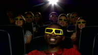 Happy multiethnic young men watching a 3-D movie in the theatre video