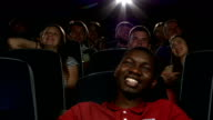 Happy multiethnic young men watching movie in the theatre video
