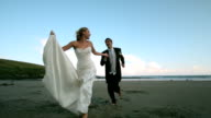 Happy newlywed couple running on the beach video