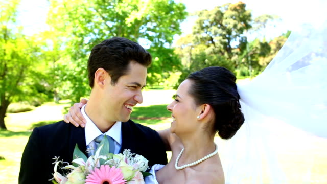 Happy newlyweds standing in the park video