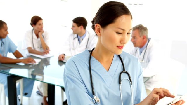 Happy nurse looking at camera with staff behind her video