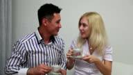 Happy Сouple drinks tea in living room video