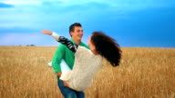 Happy сouple having fun outdoors in wheat field over sunset. Laughing Joyful Family together. Slow motion video
