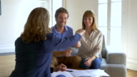 Happy owners thirty young couple receive the keys of their new house, from real-estate agent video