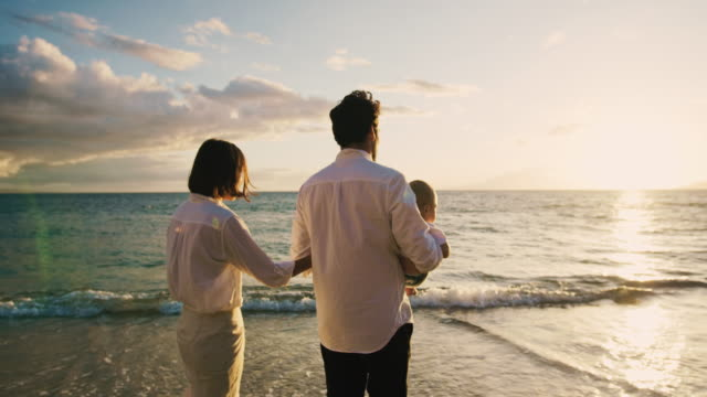 Happy parents walking on the beach at sunset with baby video