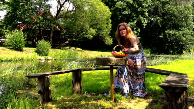 happy pregnant woman have picnic on bench near river water video