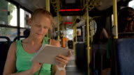 Happy pretty blonde with tablet PC riding in the bus video