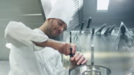 Happy professional chef in a commercial kitchen in a restaurant or hotel is preparing soup. video