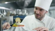 Happy professional chef in a commercial kitchen is garnishing ice cream dessert with strawberry. video