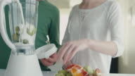 Happy romantic couple are making smoothies in blender in the kitchen at home. video