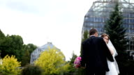 Happy romantic couple, smiling bride and groom with pink bouquet, dancing in botanic garden, glass building on background video