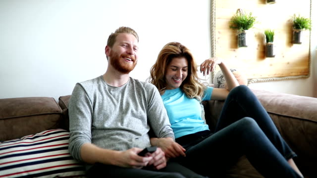 Happy romantic couple smiling having fun and watching tv video