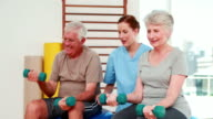 Happy senior citizens exercising with physiotherapist video