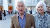 Happy Senior Couple Walking Through Outdoor Shopping Area video
