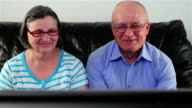 Happy senior couple watching television together video