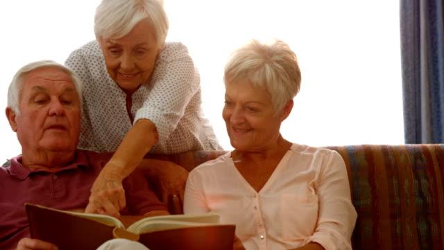 Happy senior friends reading a book video