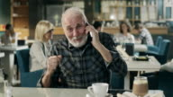 Happy senior man talking on cell phone video