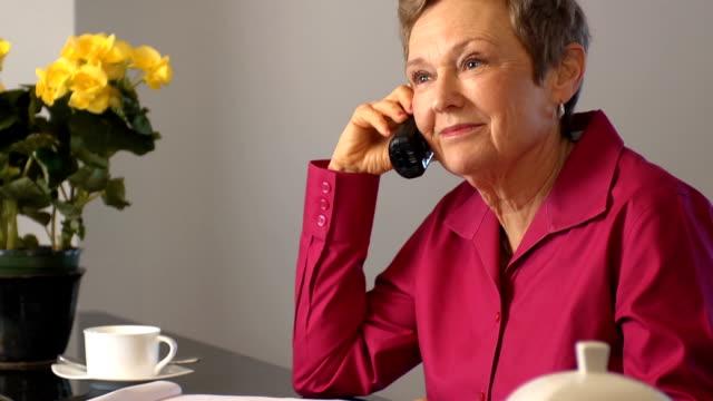 Happy Senior Woman Discusses Documents on Phone video