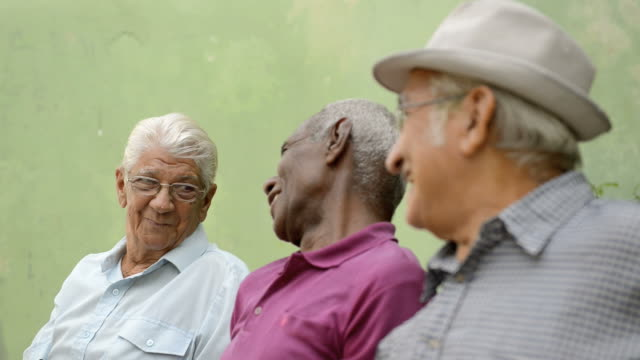 Happy seniors, old men laughing and talking in city park video