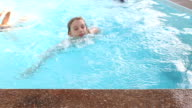 Happy similing little girl swimming in pool blue water fun video
