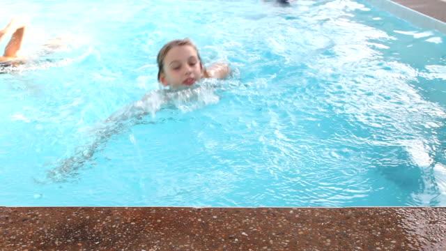 Happy similing little girl swimming in pool blue water fun video