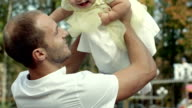 Happy smiling baby held up by his father in autumn park video