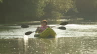 SLOW MOTION: Happy smiling couple talking and kayaking along the river at beautiful summer sunset video