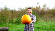Happy smiling farmer hold out vivid yellow pumpkin, slow motion video