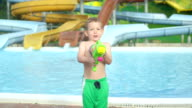 SLOW MOTION CLOSE UP: Happy smiling kid aiming and splashing water with water gun into camera in sunny summer video