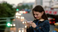 happy, smiling pretty woman uses a smartphone standing on the bridge. Wind blows her hair. FullHD video