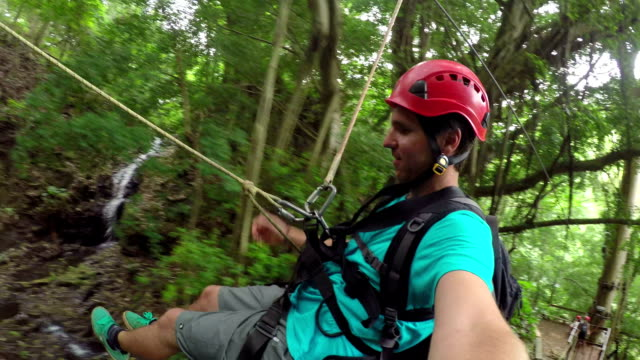 Happy smiling young man sliding on zipline in beautiful lush jungle rainforest video
