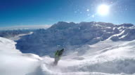 Happy snowboarder having fun riding powder snow off piste in snowy mountains video